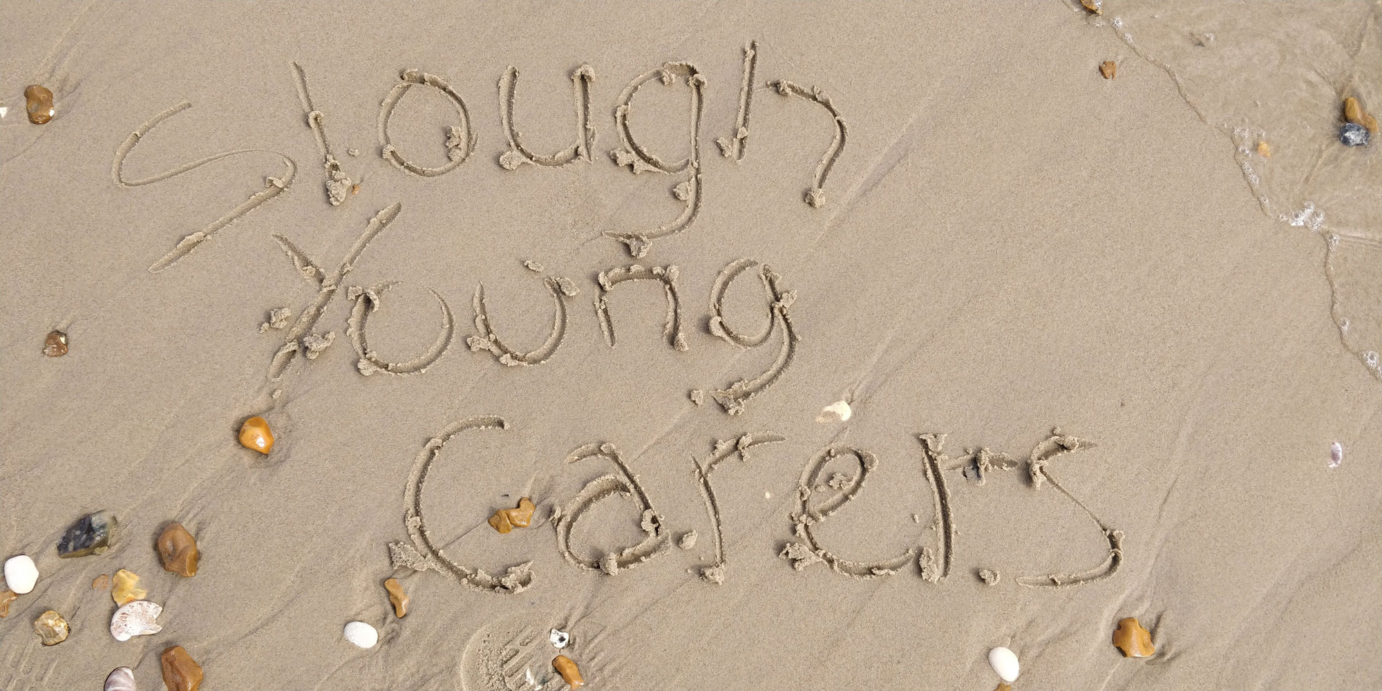Young carers written in the sand
